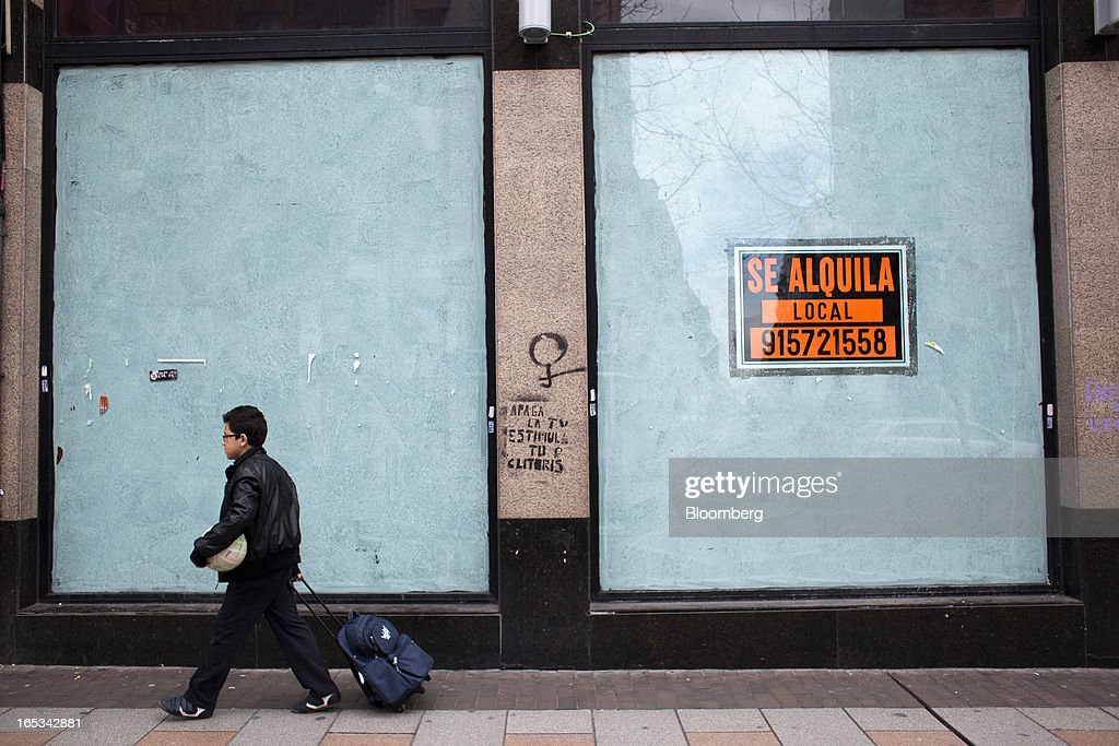 A pedestrian wheels a bag past the painted windows of a closed-down retail store in Madrid, Spain, on Wednesday, April 3, 2013. Prime Minister Mariano Rajoy told Spaniards they'll start to see the benefits of his reform program next year after he avoided becoming the fifth European leader to request a full sovereign rescue. Photographer: Angel Navarrete/Bloomberg via Getty Images