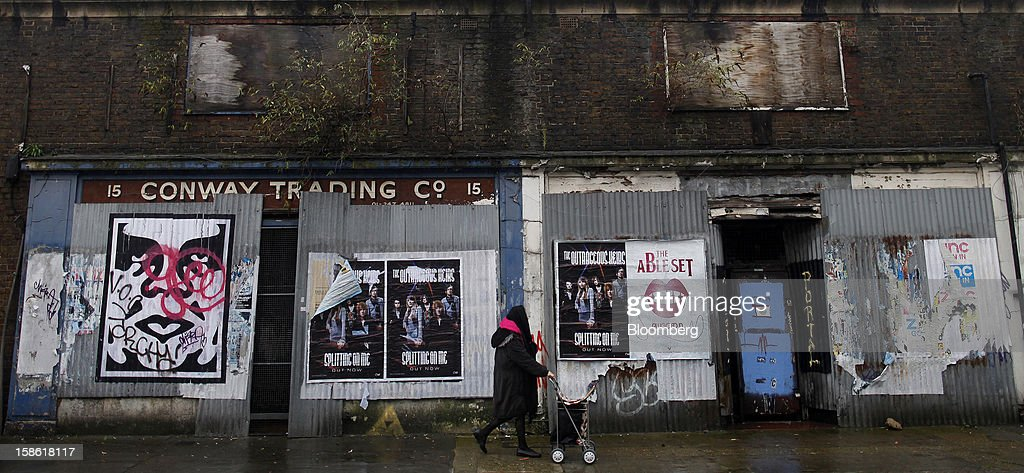 A pedestrian wheels a shopping cart past former retail stores barricaded with corrugated iron sheets in London, U.K., on Thursday, Dec. 20, 2012. Britain's economy expanded less than previously estimated in the third quarter and the budget deficit unexpectedly widened in November, complicating Prime Minister David Cameron's attempts to bolster the recovery. Photographer: Simon Dawson/Bloomberg via Getty Images