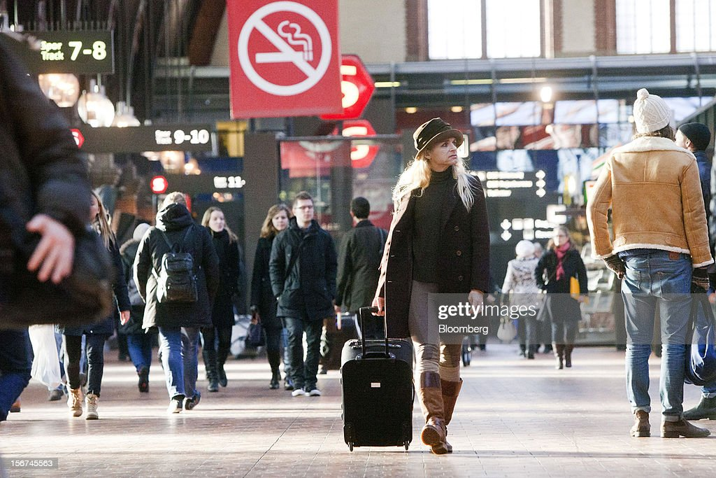 A pedestrian wheels her luggage bag along the concourse at Copenhagen central station in Copenhagen, Denmark, on Monday, Nov. 19, 2012. Denmark's two-year yields sank to the lowest in almost three months in Copenhagen trading as Europe's debt crisis continues to drive investors north. Photographer: Linus Hook/Bloomberg via Getty Images