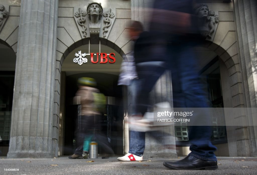 A pedestrian with a swiss flag on his shoes walks past a branch of the Swiss banking giant UBS on October 13, 2012 in Zurich. UBS could shed 10,000 jobs in the near future, according to a report in the Tages Anzeiger daily. The company could announce the layoffs when it presents its quarterly results on October 30, the newspaper said. AFP PHOTO / FABRICE COFFRINI
