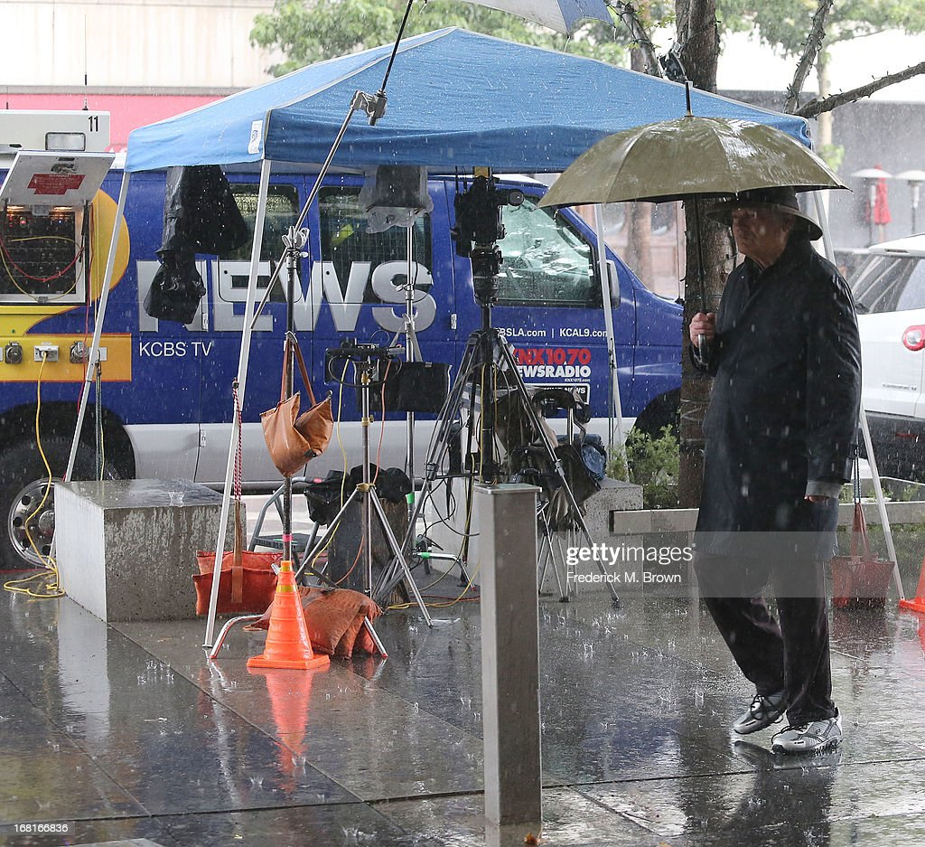 A pedestrian with an umbrella walks past a news van parked outside of the courthouse for the Jackson vs AEG Court Case, during a heavy rain storm on May 6, 2013 in Los Angeles, California.