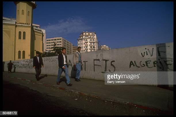 Pedestrian youths passing wall daubed w pol graffiti incl vive Algerie FIS