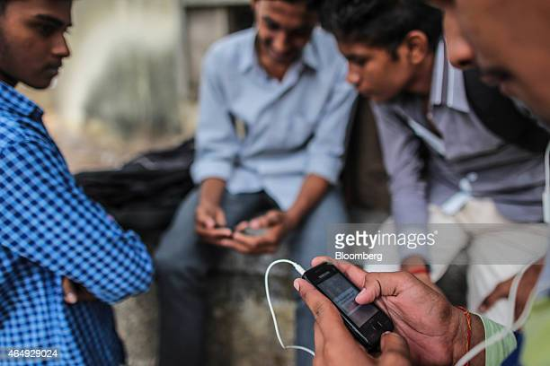 A pedestrianfront uses a Samsung Electronics Co smartphone in Mumbai India on Saturday Feb 28 2015 The government auction of telecom wireless...