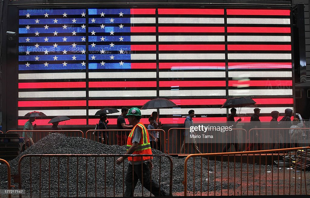 Pedestrians and a construction worker walk past a lighted American flag in the rain in Times Square on August 22, 2013 in New York City. Afternoon rain which fell today in the city is expected to mostly clear by tomorrow.