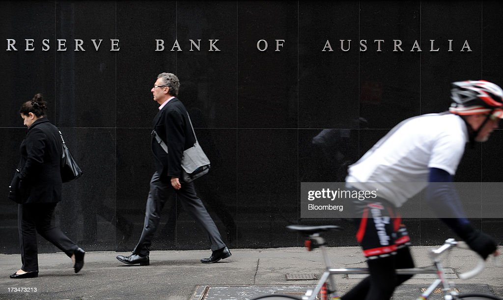 Pedestrians and a cyclist go past the Reserve Bank of Australia (RBA) headquarters in the central business district of Sydney, Australia, on Monday, July 15, 2013. While the RBA previously needed higher interest rates to control price pressures as the Australian economy expanded since 1991 without a recession, Governor Glenn Stevens has slashed the cash target, predicting a mining boom will wane. Photographer: Dan Himbrechts/Bloomberg via Getty Images