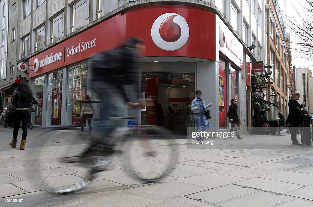Pedestrians and a cyclist pass the entrance to a Vodafone Group Plc store on Oxford Street in London, U.K., on Monday, April 8, 2013. Vodafone Group Plc is restating its results going back two fiscal years as new international accounting rules for joint ventures cut historical revenue and earnings. Photographer: Simon Dawson/Bloomberg via Getty Images