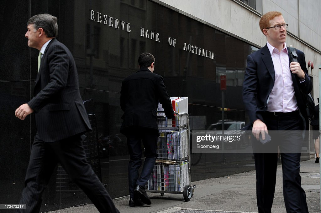 Pedestrians and a man pushing a cart of papers walk past the Reserve Bank of Australia (RBA) headquarters in the central business district of Sydney, Australia, on Monday, July 15, 2013. While the RBA previously needed higher interest rates to control price pressures as the Australian economy expanded since 1991 without a recession, Governor Glenn Stevens has slashed the cash target, predicting a mining boom will wane. Photographer: Dan Himbrechts/Bloomberg via Getty Images