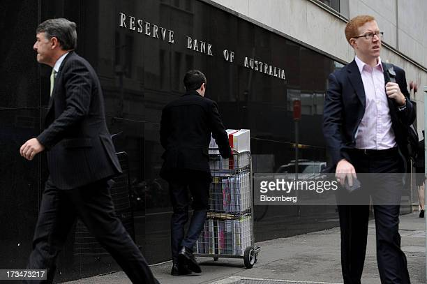 Pedestrians and a man pushing a cart of papers walk past the Reserve Bank of Australia headquarters in the central business district of Sydney...