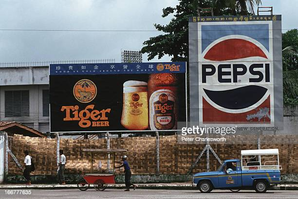 BURMA YANGON RANGOON MYANMAR Pedestrians and a street vendor pushing his vending cart pass by advertising billboards for Tiger beer and Pepsi Cola in...
