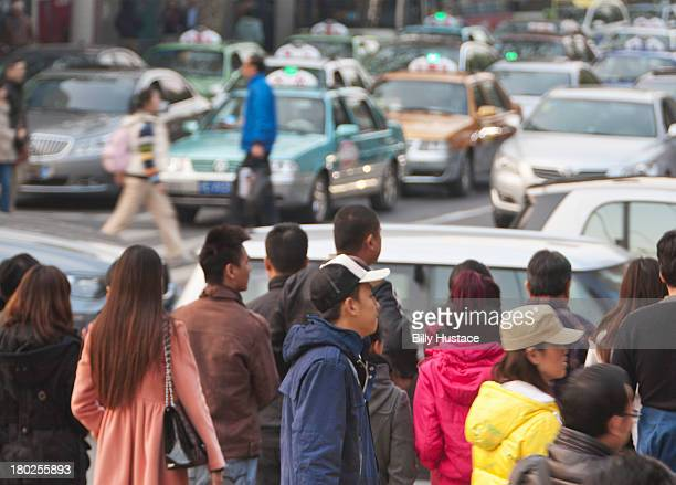 Pedestrians and cars moving on a crowded street