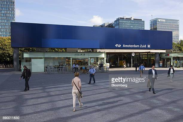 Pedestrians and city workers pass the entrance to Amsterdam Zuid railway station in the Zuidas business district of Amsterdam Netherlands on Monday...