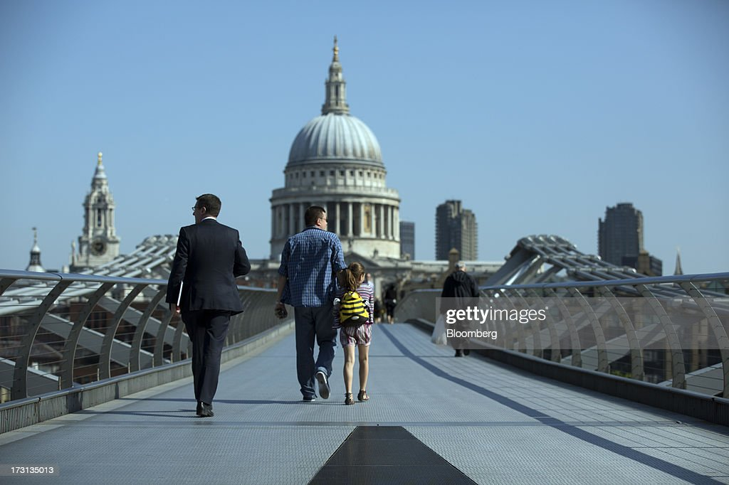 Pedestrians and commuters walk across the Millennium Bridge towards St. Paul's Cathedral in London, U.K., on Monday, July 8, 2013. Britain's economy could be in line for a period of 'strong catch-up growth' once it gets through the current weakness, according to Capital Economics Ltd. Photographer: Simon Dawson/Bloomberg via Getty Images