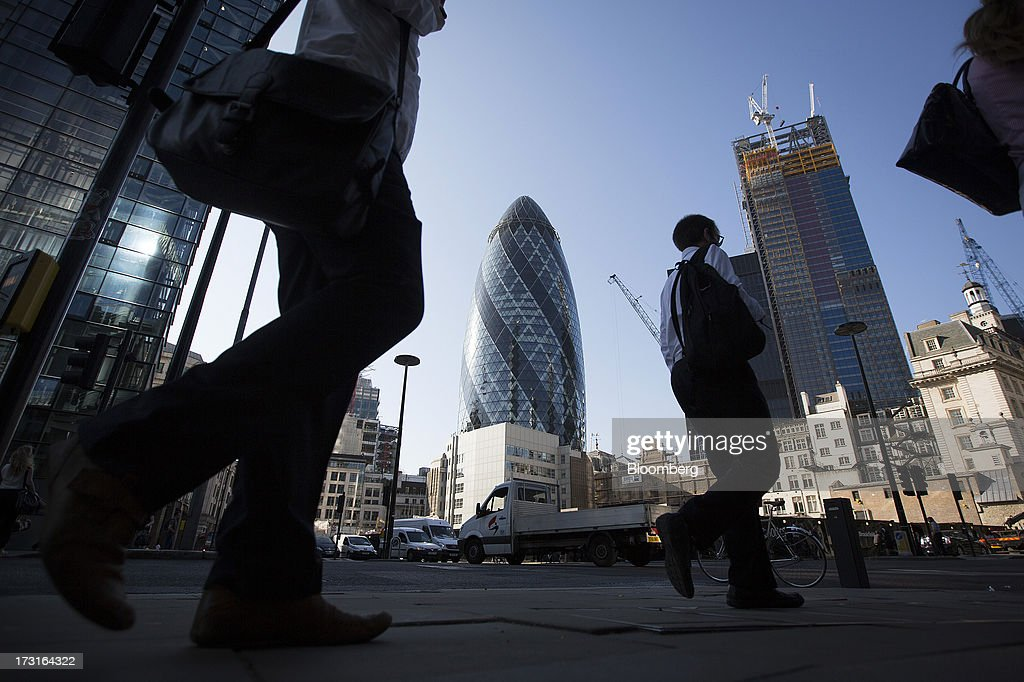 Pedestrians and commuters walk near the Swiss Re building, also known as the 'Gherkin', center, and the Leadenhall building, also known as the 'Cheesegrater', in London, U.K., on Monday, July 8, 2013. Britain's economy could be in line for a period of 'strong catch-up growth' once it gets through the current weakness, according to Capital Economics Ltd. Photographer: Simon Dawson/Bloomberg via Getty Images