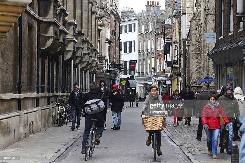 Pedestrians and cyclists pass along a shopping street in Cambridge, U.K., on Friday, March 22, 2013. In 2011, the U.K.'s government unveiled a plan to reduce state spending on higher education and shift more of the costs to students through tuition increases and a loan program. Photographer: Chris Ratcliffe/Bloomberg via Getty Images