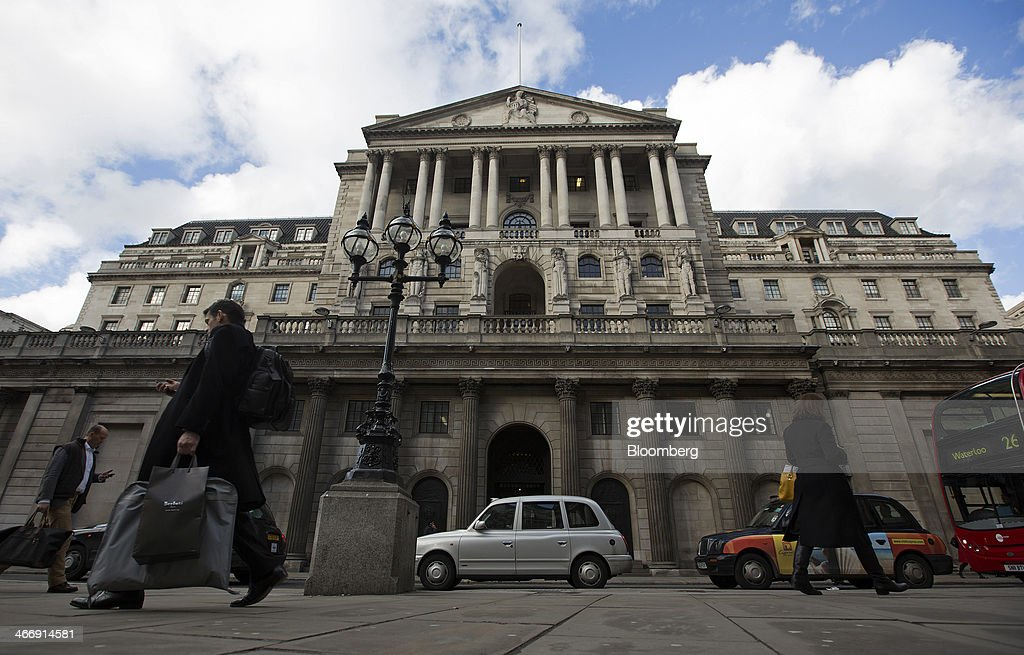 Pedestrians and London taxi cabs pass the Bank of England in London, U.K., on Tuesday, Feb. 4, 2014. Between 2007 and 2011, policy makers in London lagged behind their American counterparts in cutting rates and adopting emergency policy measures in response to the financial crisis. Photographer: Simon Dawson/Bloomberg via Getty Images