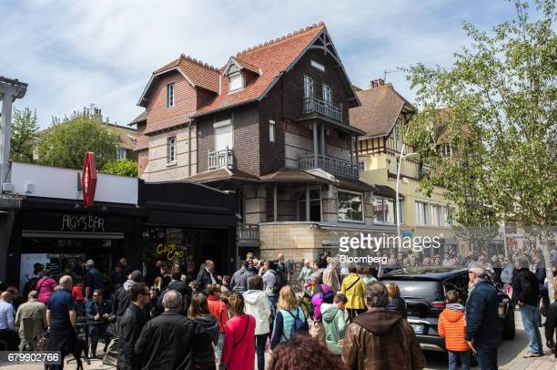 Pedestrians and members of the media gather outside the house of Emmanuel Macron French presidential candidate not pictured ahead of tomorrow's...