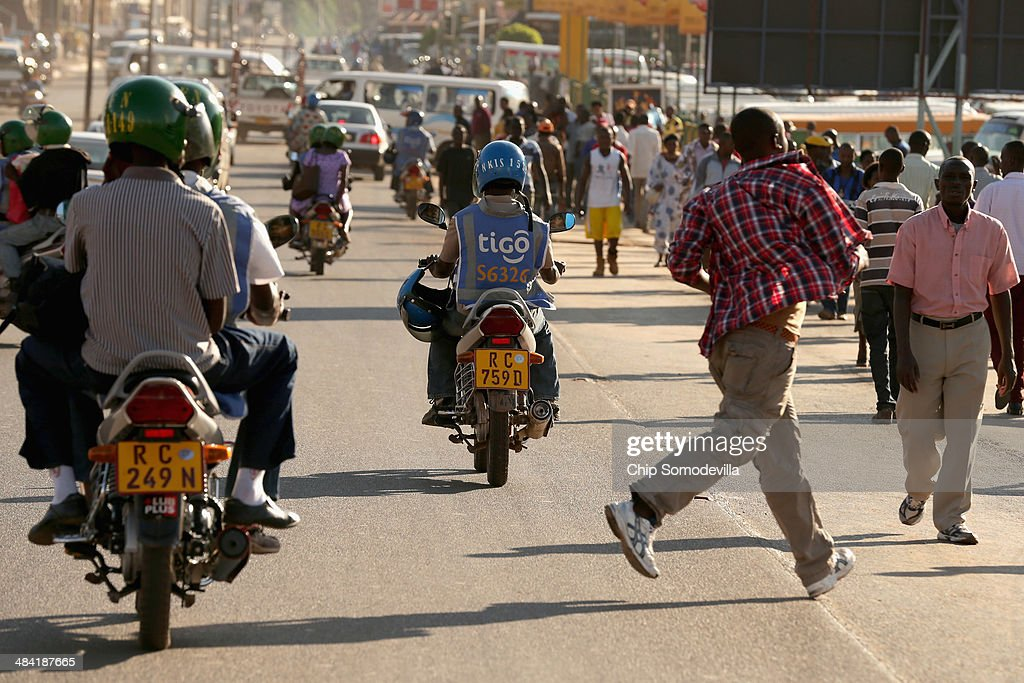Pedestrians and motorcycle taxis, called 'boda-boda' in East Africa, mix in the street near the Nyabugogo neighborhood bus park April 9, 2014 in Kigali, Rwanda. Boda-boda dominate the roads in Kigali, a city build on a serise of hills and valleys. Many drivers pay dues and belong to co-operatives which represent their interests with local and central government agencies. As motorcycles cost more than 1.3 million Rwandan Francs (or about $1900 US), many riders pay a weekly fee of about $40 US to the bike owners and keep whatever they make beyond that amount. Working 13-hour shifts, boda-boda drivers can carry about 25 passengers on a good day of business.