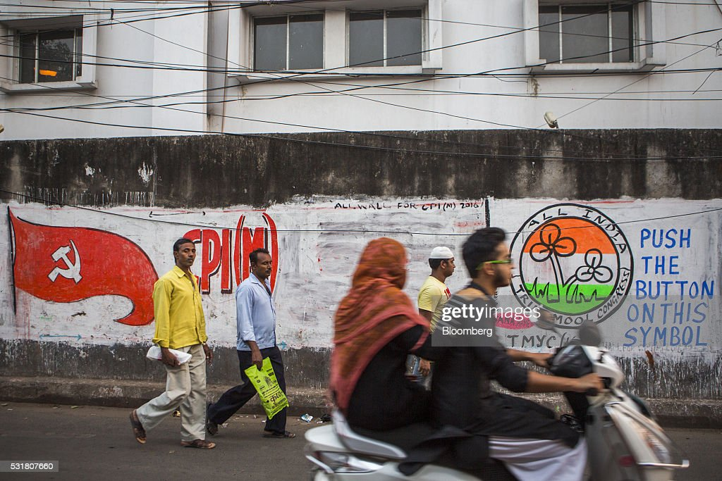 Pedestrians and motorcyclists pass murals for the Communist Party of India CPI left and the All India Trinamool Congress party in Kolkata West Bengal...