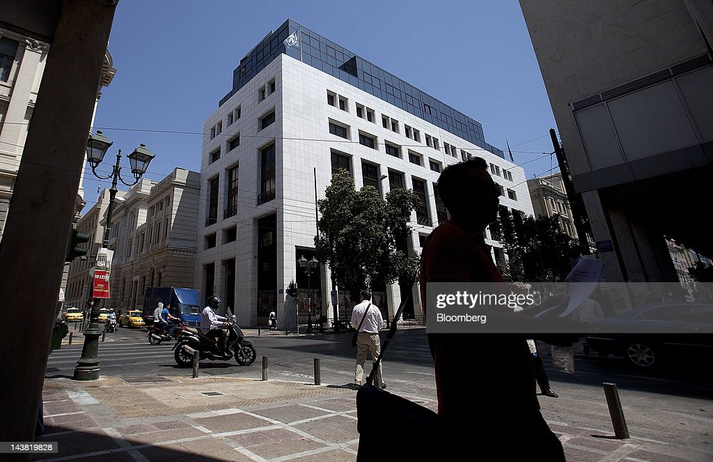 Pedestrians and motorists pass the headquarters of Alpha Bank AE in Athens, Greece, on Friday, May 4, 2012. European stocks dropped as investors awaited today's American payrolls report and elections in France, Greece, Italy and Germany this weekend. Photographer: Simon Dawson/Bloomberg via Getty Images