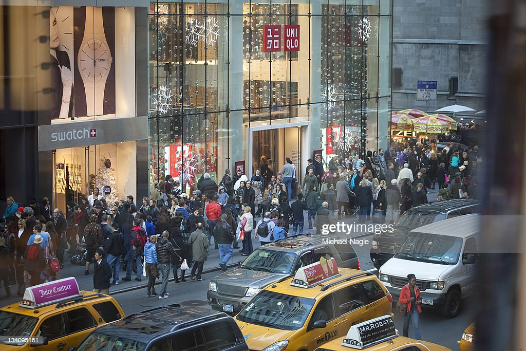 Pedestrians and shoppers fill the sidewalk on Fifth Avenue on 'Black Friday' on November 25 in New York City Marking the start of the holiday...