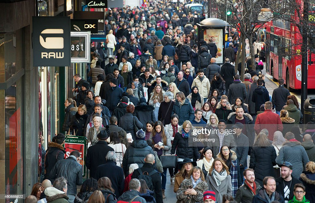 Pedestrians and shoppers pass stores and red London buses as they walk along Oxford Street in London UK on Monday Dec 29 2014 The UK may overtake...