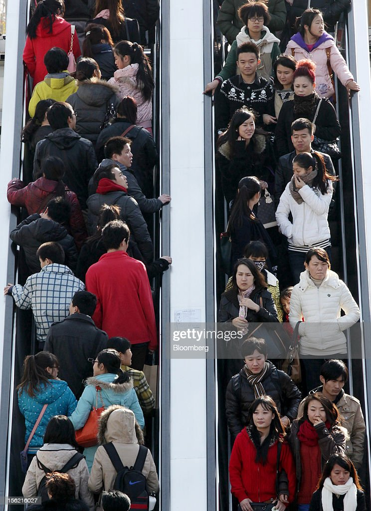 Pedestrians and shoppers ride on escalators at a shopping district in Beijing, China, on Sunday, Nov. 11, 2012. China's retail sales exceeded forecasts and inflation unexpectedly cooled to the slowest pace in 33 months, signaling the government is boosting growth without driving a rebound in prices. Photographer: Tomohiro Ohsumi/Bloomberg via Getty Images