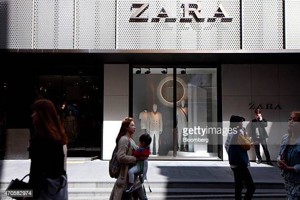 Pedestrians and shoppers walk past a Zara fashion store operated by Inditex SA in the Myeongdong shopping district of Seoul South Korea on Friday...