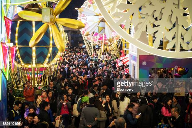 Pedestrians and shoppers walk past festive Christmas decorations near an entrance to Harbour City shopping mall operated by Wharf Holdings Ltd in the...
