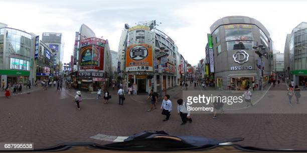 Pedestrians and shoppers walk through the Shibuya Centergai shopping street in the Shibuya area of Tokyo Japan on Wednesday May 24 2017 Japan is...