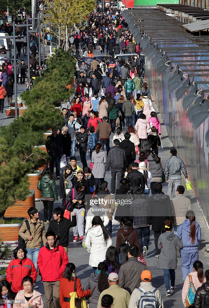 Pedestrians and shoppers walks through a shopping district in Beijing, China, on Sunday, Nov. 11, 2012. China's retail sales exceeded forecasts and inflation unexpectedly cooled to the slowest pace in 33 months, signaling the government is boosting growth without driving a rebound in prices. Photographer: Tomohiro Ohsumi/Bloomberg via Getty Images