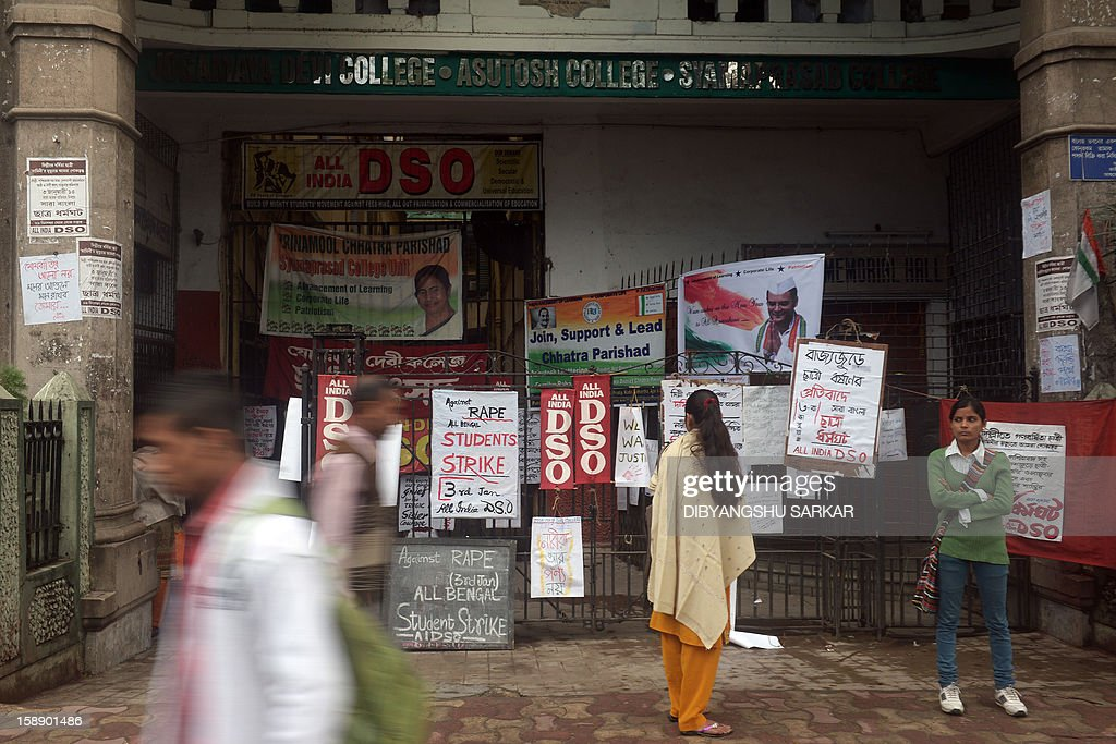 Pedestrians and students are seen in front of placards, calling for a statewide student strike against rape, in front of a government college in Kolkata on January 3, 2013. Protesters have massed in Indian cities daily since the December 16 assault demanding the government and police take sex crime more seriously, with tougher penalties for offenders and even chemical castration being considered. Indian police formally charged five men with murder, kidnapping and rape January 3 in a New Delhi court over the fatal gang-raping of a woman that has appalled the nation. AFP PHOTO/Dibyangshu SARKAR