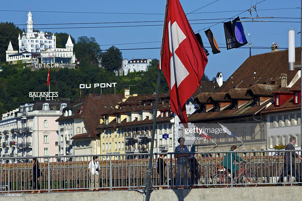 Pedestrians and tourists walk near a Swiss national flag as it flies from a bridge over the River Reuss in Lucerne, Switzerland, on Saturday, Aug. 10, 2013. The Swiss National Bank will abolish its franc ceiling once it starts raising interest rates, Vice President Jean-Pierre Danthine said. Photographer: Gianluca Colla/Bloomberg via Getty Images