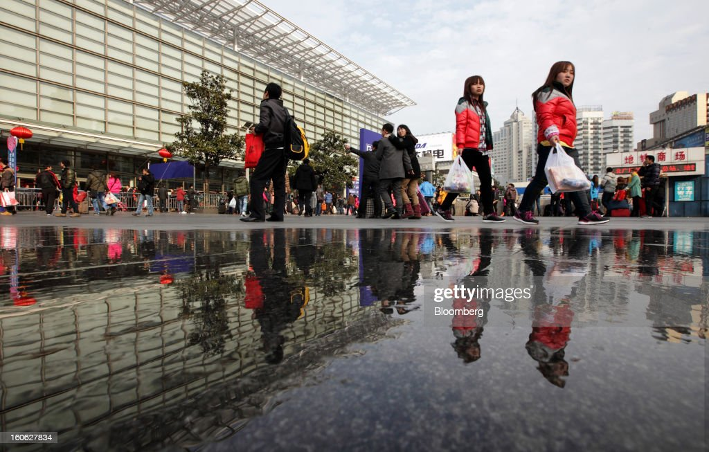 Pedestrians and travelers walk outside Shanghai Railway Station in Shanghai, China, on Sunday, Feb. 3, 2013. Forecasts of snow and rain across China threaten to disrupt the travel plans of millions of Chinese heading home for the Lunar New Year holidays that start Feb. 9, the national weather agency warned. Photographer: Tomohiro Ohsumi/Bloomberg via Getty Images
