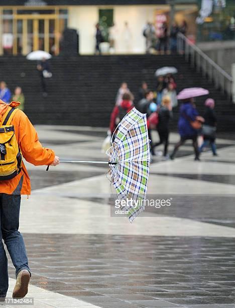 Pedestrians and umbrella in har d wind