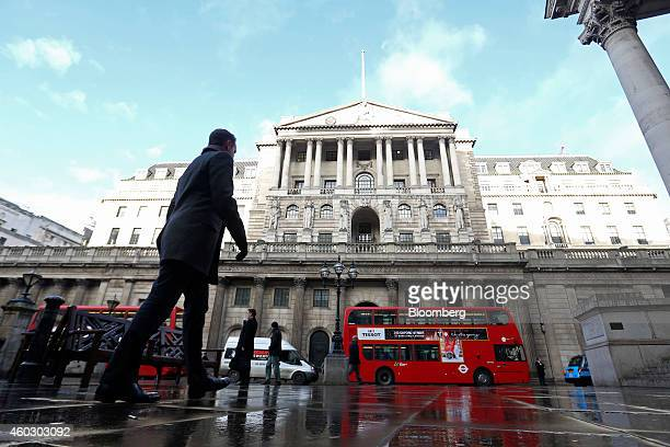 Pedestrians and vehicles including a red London bus pass the front entrance of the Bank of England in London UK on Thursday Dec 11 2014 The Bank of...