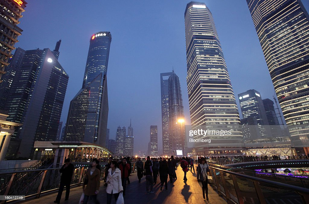 Pedestrians and workers walk on an overpass past commercial buildings at dusk in the Pudong area of Shanghai, China, on Wednesday, Jan. 30, 2013. China's economic growth accelerated for the first time in two years as government efforts to revive demand drove a rebound in industrial output, retail sales and the housing market.Photographer: Tomohiro Ohsumi/Bloomberg via Getty Images
