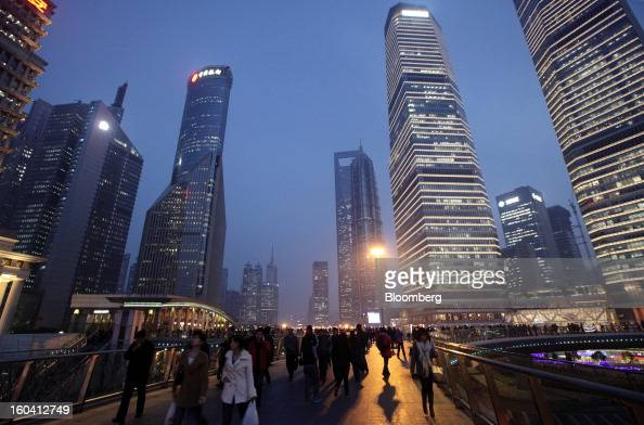 Pedestrians and workers walk on an overpass past commercial buildings at dusk in the Pudong area of Shanghai China on Wednesday Jan 30 2013 China's...