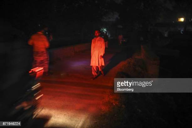 Pedestrians are illuminated by the tail light of a motorcycle on a road at night in Varanasi Uttar Pradesh India on Friday Oct 27 2017 In Varanasi...