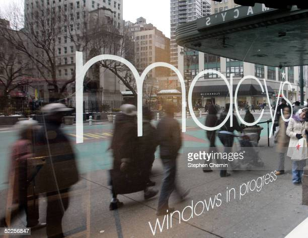 Pedestrians are reflected in a Macy's window February 28 2005 in New York City Federated Department Stores Inc is buying rival May Department Stores...