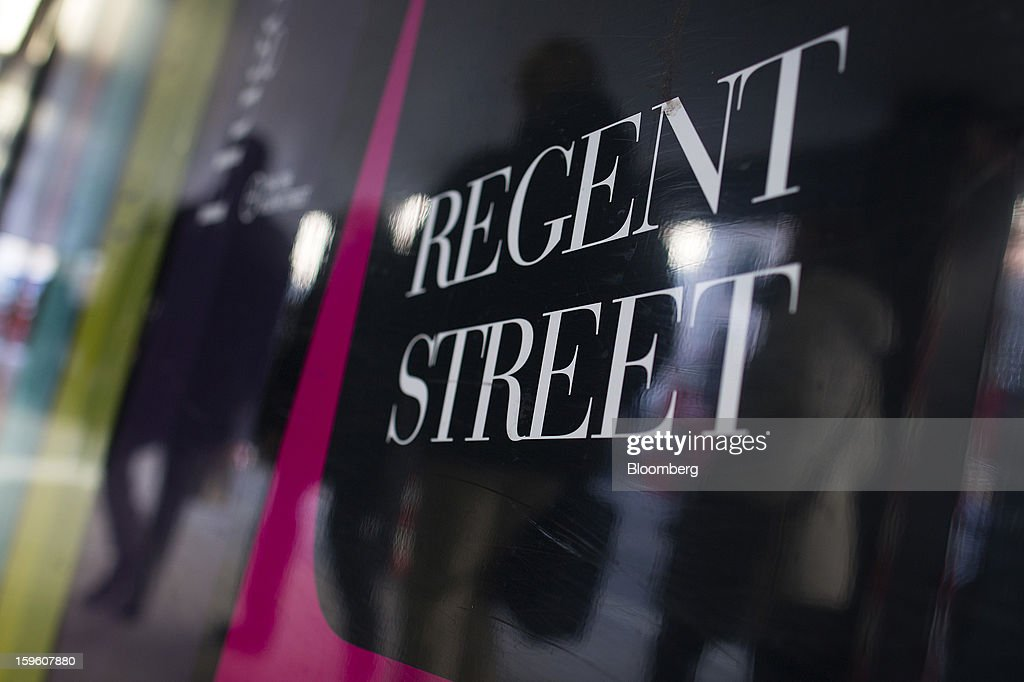 Pedestrians are reflected in a sign advertising the Regent Street shopping district on a commercial real estate redevelopment in central London, U.K., on Thursday, Jan. 17, 2013. The pound weakened to a nine-month low against the euro as investors favored assets in the 17-member currency region, betting the struggling U.K. economy will weigh on sterling. Photographer: Simon Dawson/Bloomberg via Getty Images