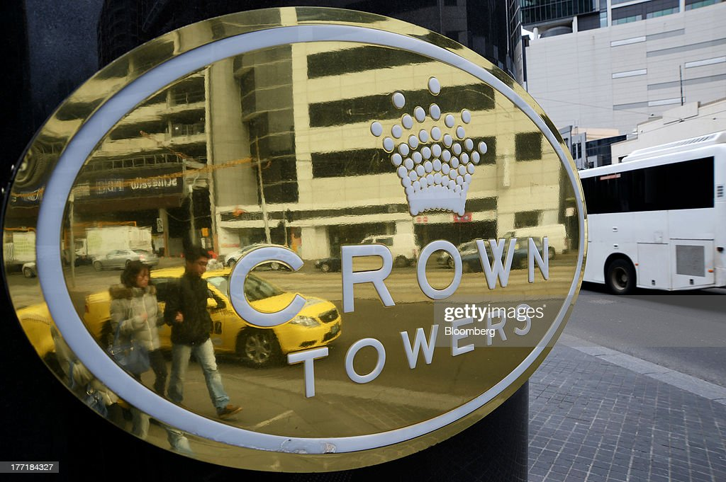 Pedestrians are reflected in a sign for the Crown Towers hotel, part of the Crown Melbourne casino and entertainment complex operated by Crown Ltd., in Melbourne, Australia, on Wednesday, Aug. 21, 2013. Crown Ltd., the gaming company controlled by billionaire James Packer, is scheduled to announce full-year results on Aug. 23. Photographer: Carla Gottgens/Bloomberg via Getty Images