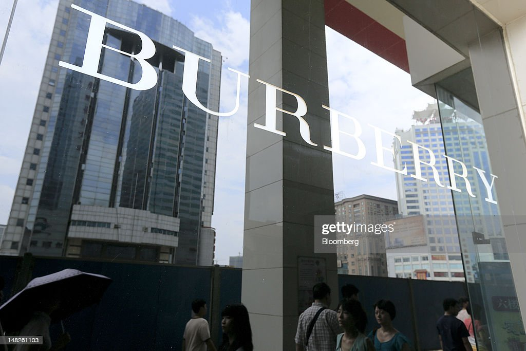 Pedestrians are reflected in a window advertising Burberry Group Plc luxury products in Changsha, Hunan Province, China, on Friday, July 13, 2012. Gross domestic product (GDP) expanded 7.6 percent in the second quarter of 2012 from a year earlier, China's National Bureau of Statistics said today in Beijing. Photographer: Nelson Ching/Bloomberg via Getty Images