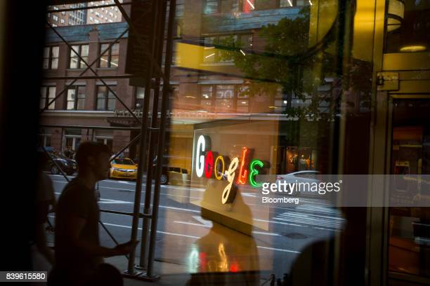 Pedestrians are reflected in a window looking into a lobby of the Google Inc offices in New York US on Tuesday Aug 22 2016 WalMart Stores Inc is...