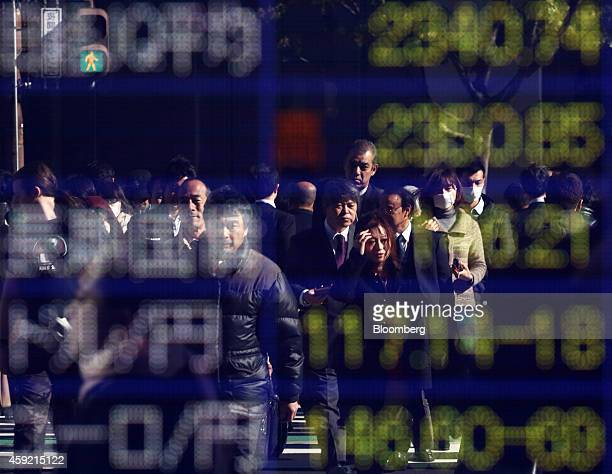 Pedestrians are reflected in an electronic board displaying the exchange rate of the yen against the euro bottom and one against the US dollar second...