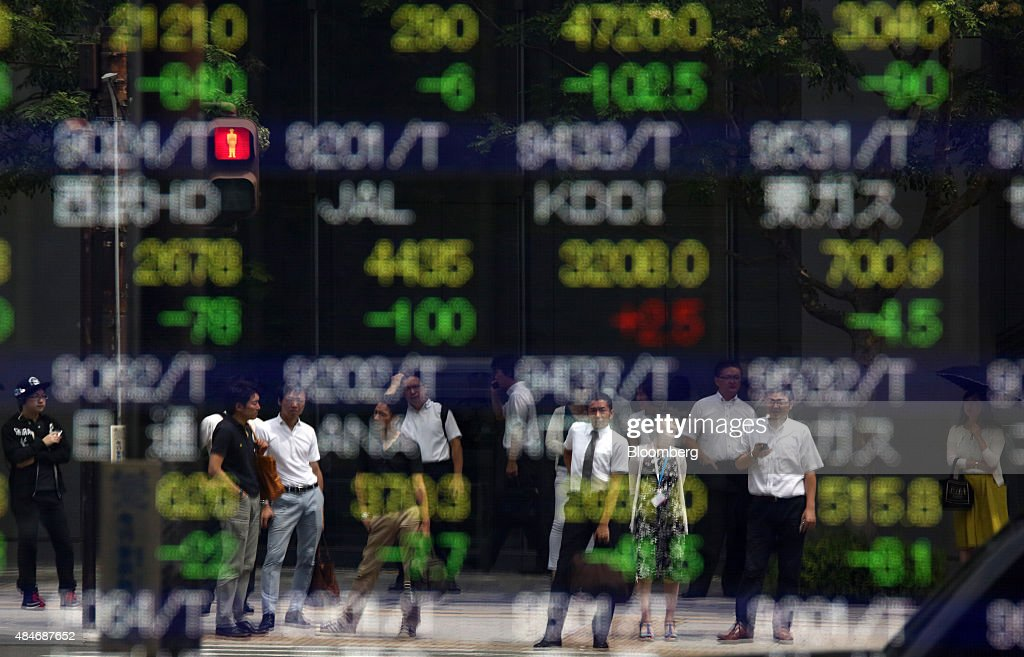 Pedestrians are reflected in an electronic board outside a securities firm in Tokyo Japan on Friday Aug 21 2015Japanese stocks plunged with the Topix...
