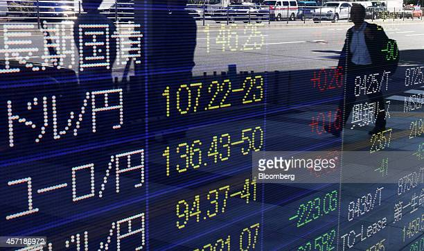 Pedestrians are reflected in an electronic stock board displaying the exchange rate of the yen against the US dollar center and the euro bottom...