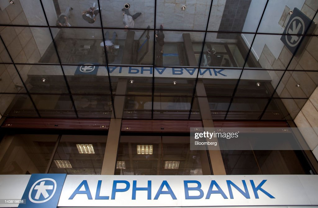 Pedestrians are reflected in the glass ceiling above an Alpha Bank AE branch in Athens, Greece, on Friday, May 4, 2012. European stocks dropped as investors awaited today's American payrolls report and elections in France, Greece, Italy and Germany this weekend. Photographer: Simon Dawson/Bloomberg via Getty Images