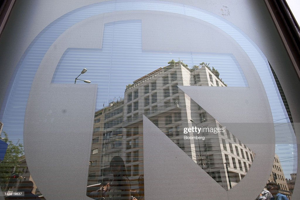 Pedestrians are reflected in the logo of Alpha Bank AE on the window of a branch in Athens, Greece, on Friday, May 4, 2012. European stocks dropped as investors awaited today's American payrolls report and elections in France, Greece, Italy and Germany this weekend. Photographer: Simon Dawson/Bloomberg via Getty Images