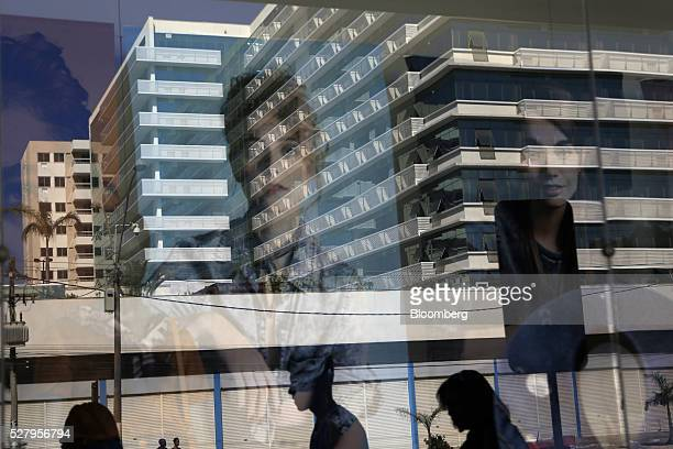 Pedestrians are reflected in the window of a clothing shop across from an empty office building in Itaborai Brazil on Tuesday April 12 2016 Just 30...