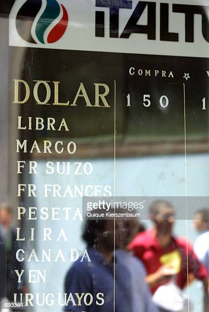Pedestrians are reflected in the window of a currency exchange house January 12 2002 in Buenos Aires Argentina Currency Exchange offices were...